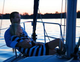 Portrait photography of a couple on a boat with sunset.