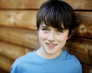 Outdoor portrait photography of a young boy with a blue shirt on.