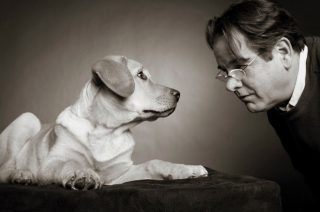 Black and white pet photography lighting of a man and his Golden Retriever taken in a Guelph studio.