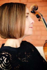 A musician being photographed with her violin by Trina Koster, Guelph.