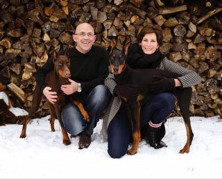 Outdoor pet and family photography of a couple and two Doberman Pinschers.