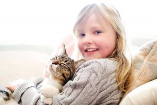 A young girl and her cat, taken by pet photographer Trina Koster at their home.