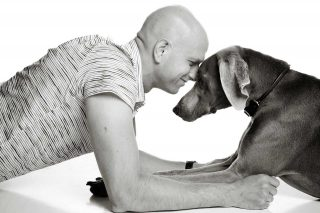 Studio pet photography of a man and Weimaraner dog nose to nose.
