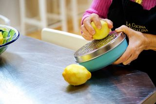 Product photography of a woman preparing lemons for a cookbook recipe.