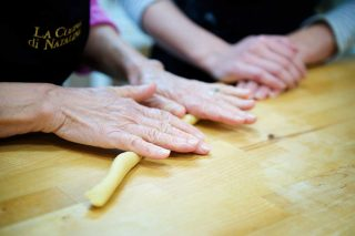 Editorial photo of grandmother and granddaughters hands preparing food in a commercial kitchen in Guelph.