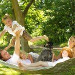 Outdoor family portrait with dog taken on hammock in Fergus, Ontario.