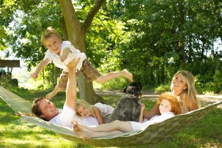 Outdoor family portrait with dog taken on hammock in Fergus, Ontario.