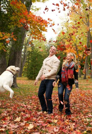 Fall family portrait with their pet jumping around in the leaves in Elora, Ontario.