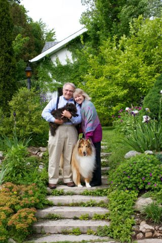 Pet and family photography of two dogs with their owners on the front steps on their house in Fergus, Ontario.