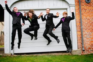 Groom and bestmen jumping for action photography at wedding.