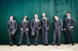 Country wedding photography of bestmen standing against a turquoise wall.