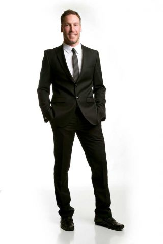 A male model portraying a young business man in a suit.