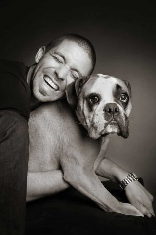 Professional pet photography of a man hugging his Boxer dog in a studio in Guelph.