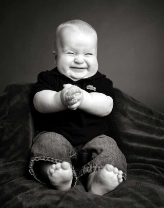 Chubby, six month old baby getting black and white photograph done in studio by Trina Koster.