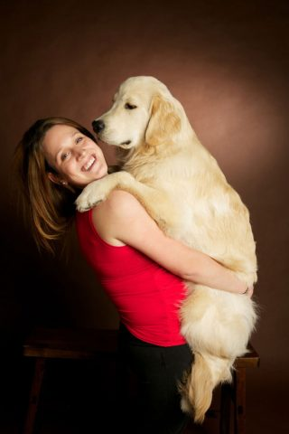 Pet family photo of a woman holding a large Golden Retriever in a studio.