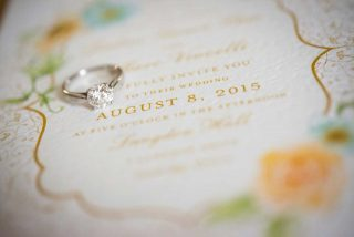 A wedding ring laid out over a wedding invitation to Langdon Hall.
