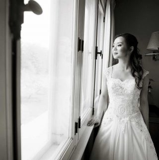 Black and white Langdon Hall wedding photography of a bride looking out a window.