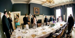 Guests having wedding reception in the Colonel Langdon dining room, taken by wedding photographer Trina Koster.