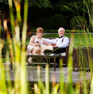 Couple having a glass of wine by the Lily Pond at Langdon Hall.