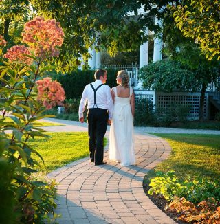 Bride and groom walking down stone pathway in the Langdon Hall garden.