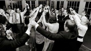 Guests dancing in a circle inside of wedding reception room.