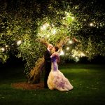 Bride and groom dancing in front of a brightly lit tree outside of Langdon Hall.
