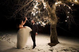 Married couple dancing by tree with lights at night time, by Langdon Hall wedding photographer Trina Koster.