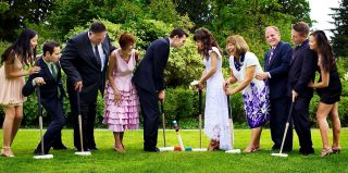 Newly weds and guests playing croquette on the Langdon Hall green in Cambridge, Ontario.