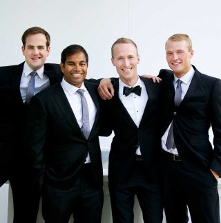 Husband and his close friends posing with suits on before wedding.
