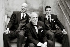 The men of the family posing for a black and white photo on the steps to the Orchard Room near Langdon Hall.