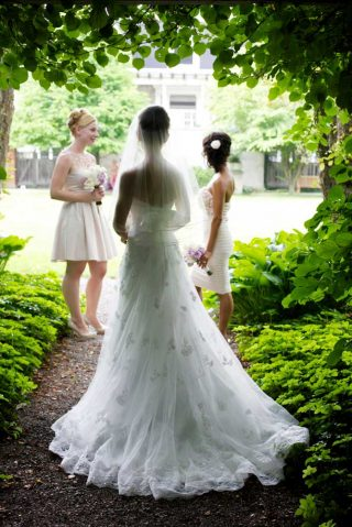 Bride in her wedding dress walking beneath green foliage.