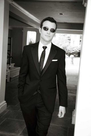 Groom in his suit and tie with sunglasses on looking ready for the wedding party.