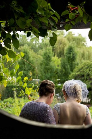 Bride and mother sitting on bench overlooking the organic garden at Langdon Hall.