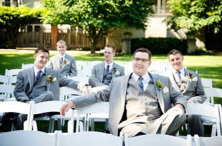 Groom and his best men sitting on white chairs on Langdon field.