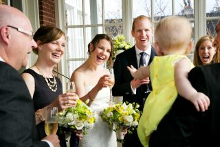 Family of the bride gather around a baby wearing a yellow dress after the wedding.