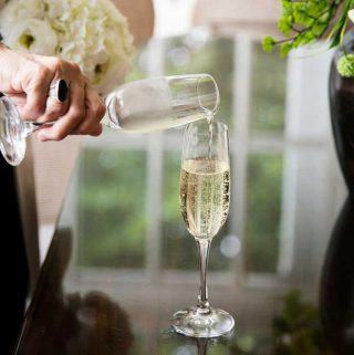 White wine being poured in glass during wedding reception.