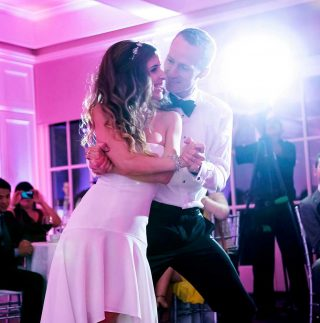 Bride and groom dancing in the Orchard Room at Langdon Hall with pink lighting.