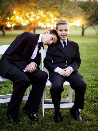 Brothers of the groom sitting on a bench on the Langdon field.