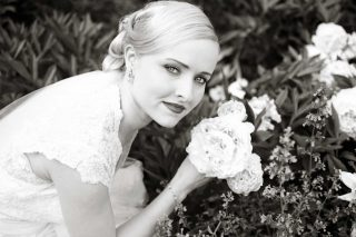 Wife posing for black and white wedding photography with some flowers at the garden.