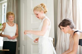 Soon to be wife of the groom getting her dress fitted.