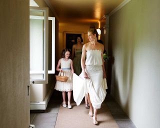 Flower girl and bride walking through the hallway captured by wedding photographer Trina Koster.