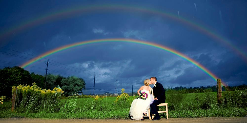 Wedding photography of a couple kissing with a double rainbow in the background.