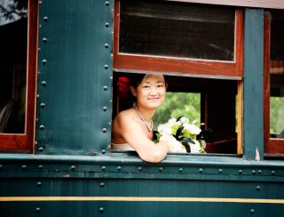 Bride looking out the window towards Waterloo wedding photographer Trina Koster.