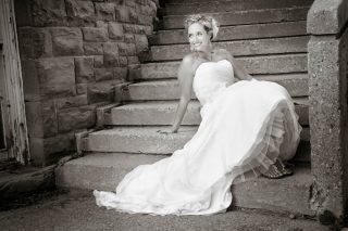 Bride in her wedding dress sitting on steps.