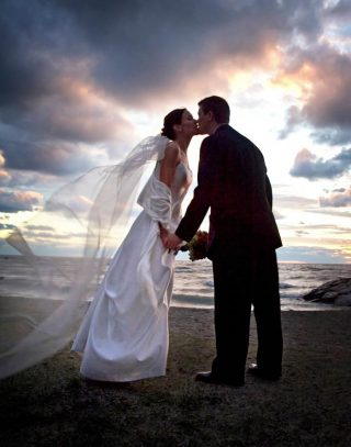 Husband and wife in her wedding dressed sharing a kiss on a beach.