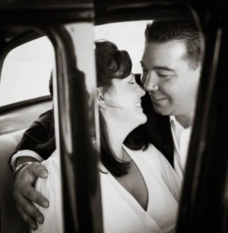 Couple kissing in the back seat of a car after their wedding.