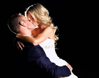 Husband and wife kissing with a black background taken by a Guelph wedding photographer.