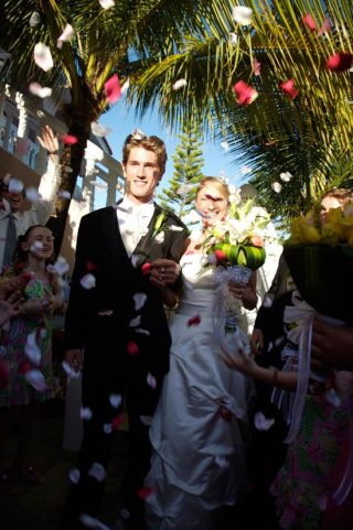 Couple walking down the aisle as flower petals are thrown in front of them.