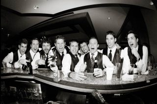 Groom and his bestmen dressed in white shirts and vests having drinks at the wedding bar.